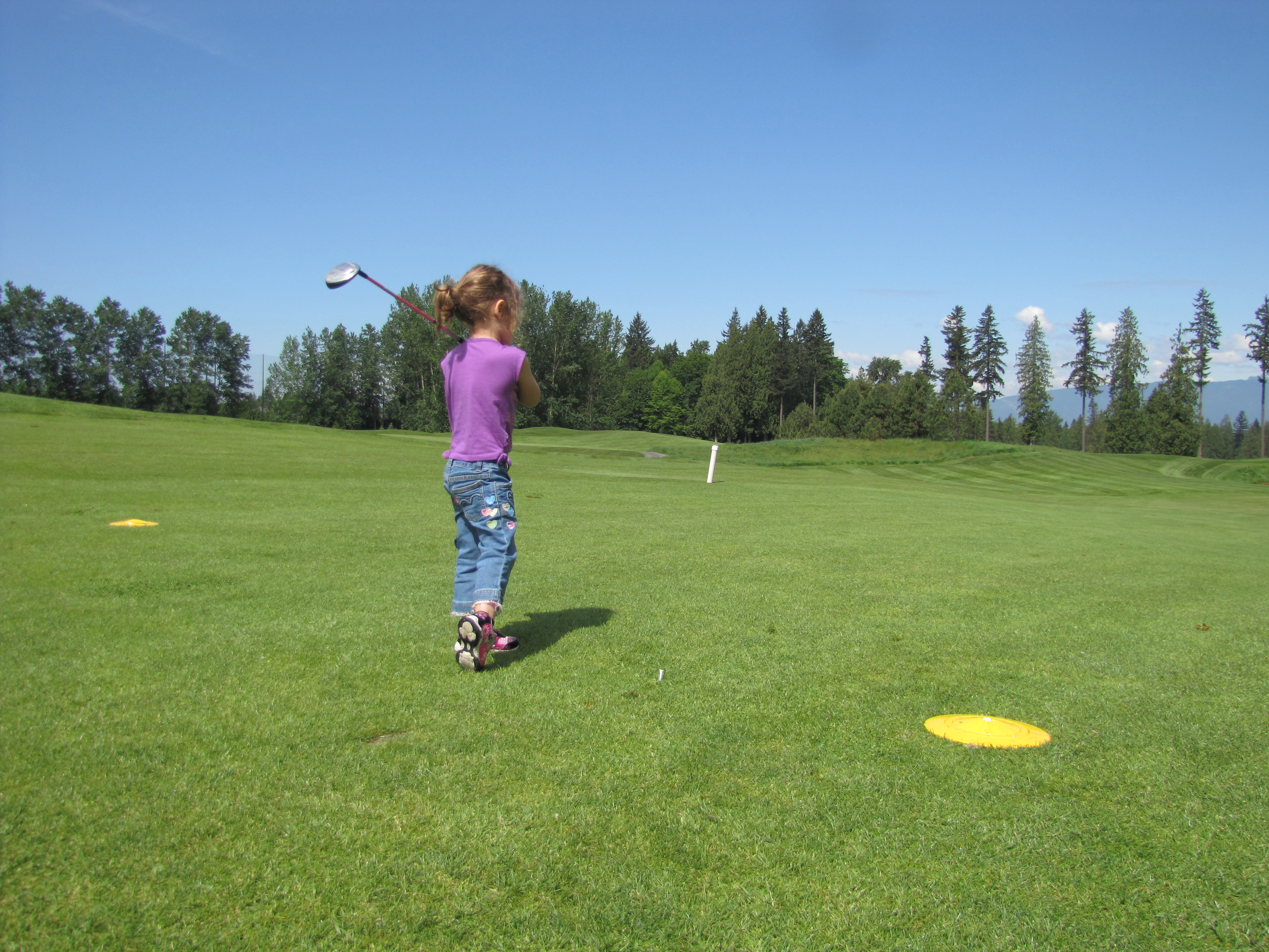 Little girl playing golf swinging the club